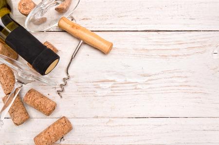corcho: Botella de vino, sacacorchos y corchos en mesa de madera. Fondo Foto de archivo