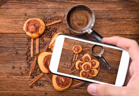 camera: Hands taking photo cinnamon rolls with smartphone.