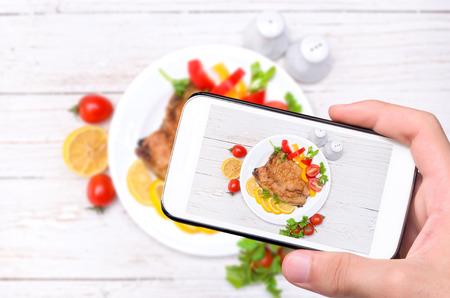 tomando refresco: Manos que toman pescado foto con el teléfono inteligente