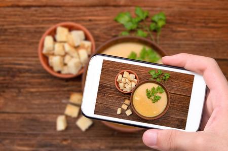 comidas saludables: Manos tomar la foto de la sopa de guisantes con el teléfono inteligente.