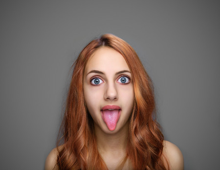Girl showing tongue isolated on gray.