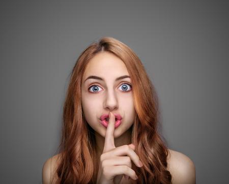 dedo: Chica manteniendo el dedo en sus labios, aislado en gris. Foto de archivo