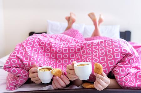 joven pareja feliz que come el desayuno en la cama.