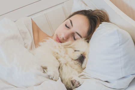 nap: Girl and her dog in the bed.