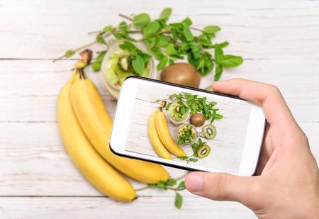 tomando refresco: Manos tomar la foto de postre con frutas y queso crema en un tarro de cristal con el tel�fono inteligente.