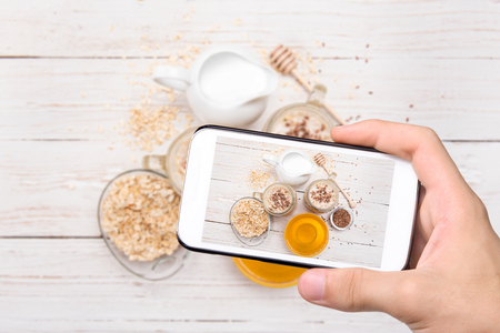 taking refreshment: Hands taking photo smoothies with oatmeal with smartphone.