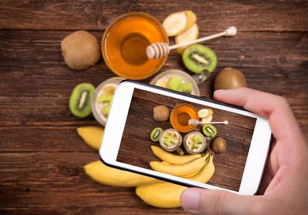 tomando refresco: Manos tomar batidos de fotos con la harina de avena con el tel�fono inteligente. Concepto de la cocina.
