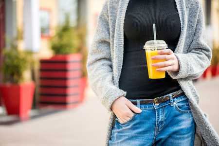Portrait of young stylish hipster girl walking on the street, drinking tasty smoothie. Фото со стока