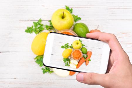 tomando refresco: Manos tomar batidos de fotos con las zanahorias, manzana, limón, perejil con el teléfono inteligente.