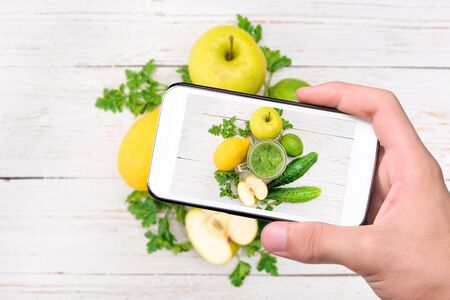 tomando refresco: Hands taking photo smoothies with cucumber, apple, lemon, parsley with smartphone.