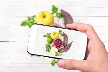 tomando refresco: Manos tomar batidos de fotos con la remolacha, manzana, limón, perejil con el teléfono inteligente.