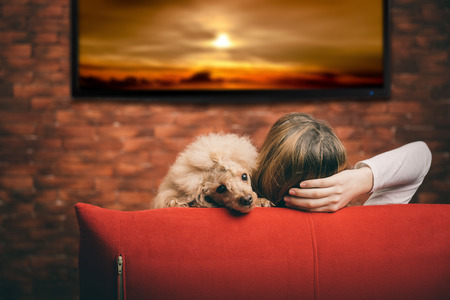 Young woman watching smart TV with dog.