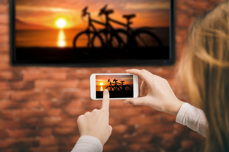 Closeup of a smart phone is connected to a smart TV.