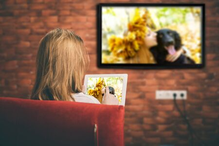 Closeup of a tablet is connected to a smart TV. Stock Photo