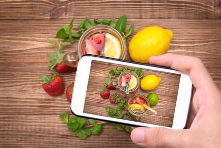 tomando refresco: Manos tomar la bebida de la foto con la fresa en vidrio con el teléfono inteligente. Foto de archivo