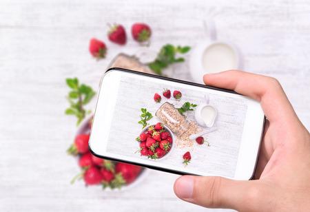 tomando refresco: Manos tomar batidos de fotos con la harina de avena, fresa en vidrio con el teléfono inteligente.