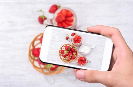 tomando refresco: Manos tomar la foto con el postre de fresas y queso crema en un tarro de cristal con el teléfono inteligente.