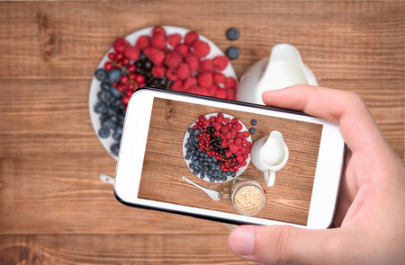 Hands taking photo smoothies with oatmeal, berries in glass with smartphone.