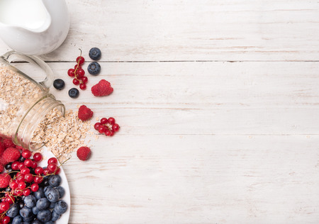 oatmeal: Smoothies with oatmeal, berries in glass jars on a wooden background.