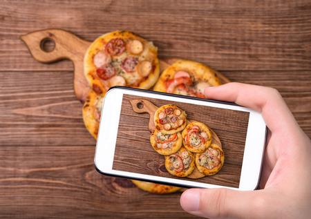 Hands taking photo mini pizza with smartphone.