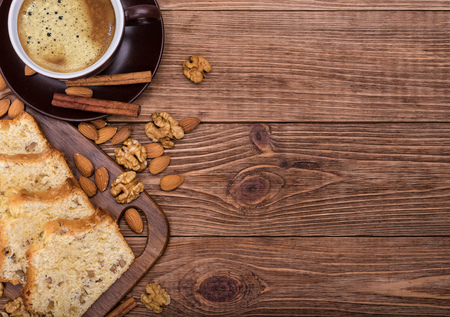 homemade cake: Homemade nut cake with cup of coffe on wooden background.