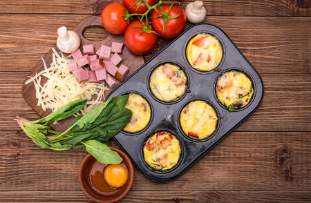 Delicious egg muffins with ham, cheese and vegetables. Concept of cooking.