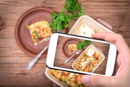 Hands taking photo chicken lasagna and white cheese with smartphone.