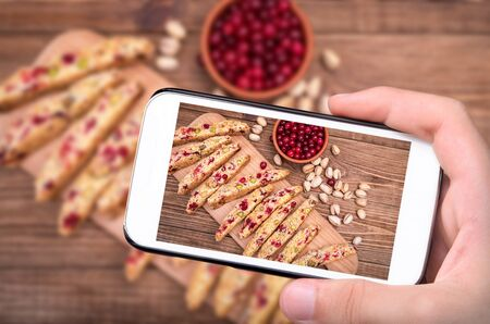 Hands taking photo biscotti with pistachios and cranberries with smartphone.