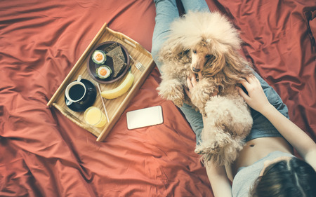 Young woman is lying in bed with dog and having a healthy breakfast.