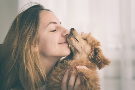 Young girl kissing her good friend dog. Positive human emotions. Standard-Bild