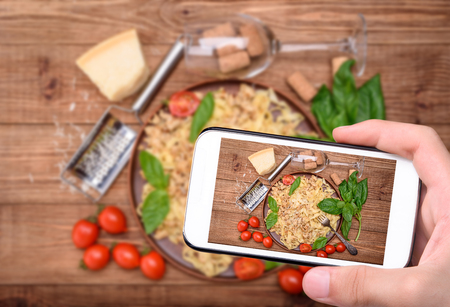 Hands taking photo traditional Italian pasta, served with a meat-based sauce with smartphone.