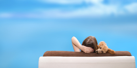 Woman with her dog relaxing on the sofa.