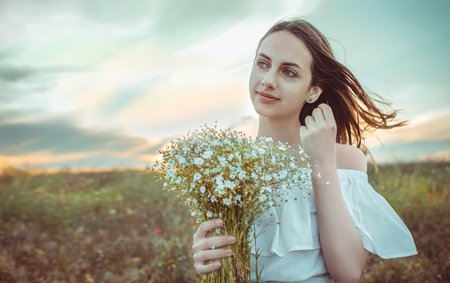 Beautiful girl standing in a field holding a bouquet of white flowers in her hands.