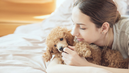 Jonge vrouw ligt en slapen met poedel hond in bed.