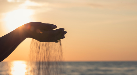 Sand running through a woman's hands. Imagens