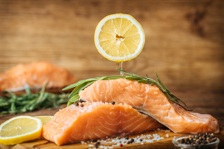 Lemon juice drips on the raw salmon fish fillet on a wooden background. Imagens