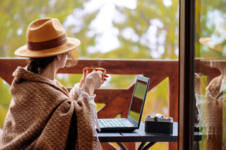 Freelancer woman sits at the terrace with a laptop.