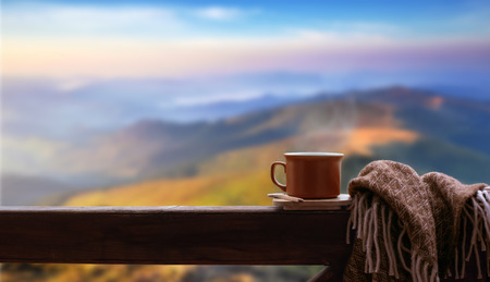 Cup of tea on the wooden railing. Mountains