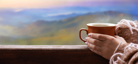 Hands holding hot cup of tea. Mountains