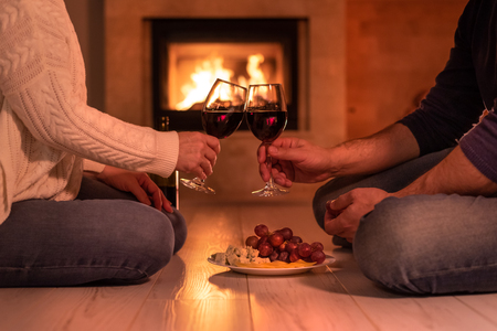 Young couple have a romantic dinner with wine over fireplace Фото со стока