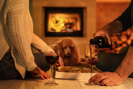 Young couple having romantic dinner with pizza and wine over fireplace