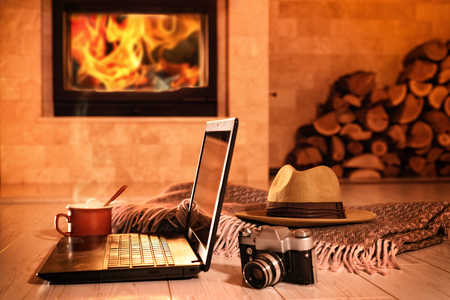 Laptop or notebook, hat, camera, cup on the fireplace