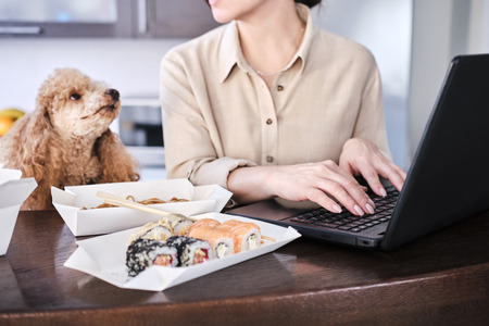 Freelancer woman tasting asian food at workplace.