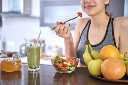 Woman eating salad after workout.