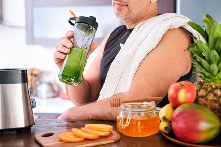 Adult man drinking smoothie in home kitchen after a workout. Фото со стока
