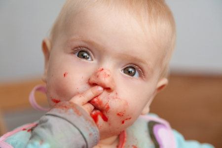 dirty girl: baby girl eating, dirty face Stock Photo