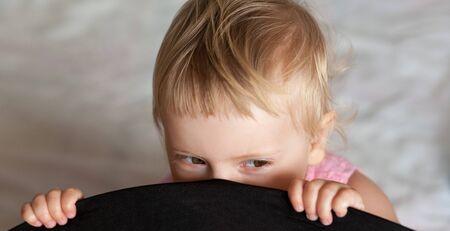prank: baby girl is hiding, childish prank  Stock Photo