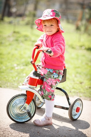 little girl standing on road with her tricycle photo