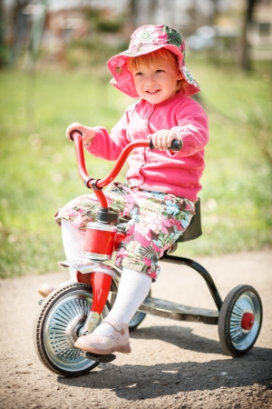 little girl driving her tricycle smiling