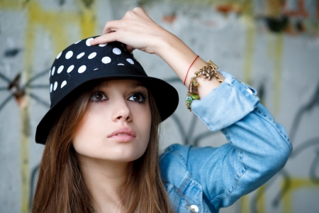 portrait of young female outdoors touching her hat with fingers looking above photo